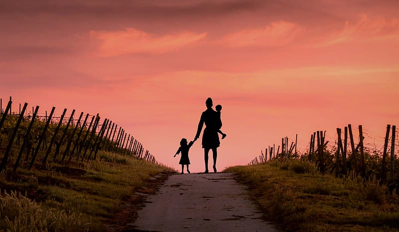 Silhouette of woman holding girl and carrying baby