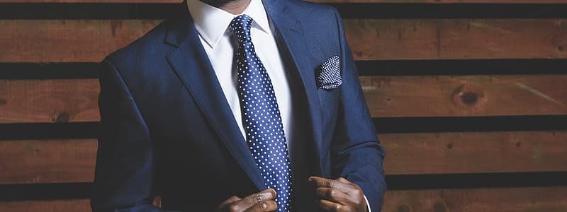 Man in black suit jacket and blue and white polka dot necktie