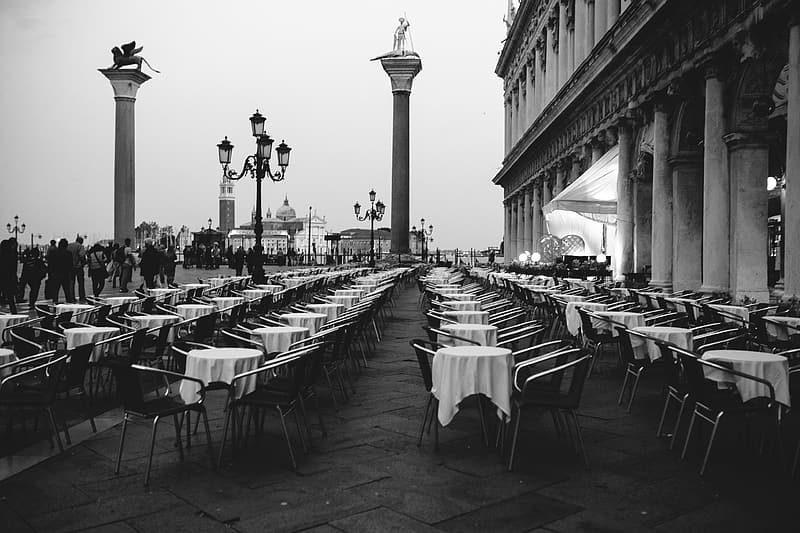 Grayscale photo of dining tables and chairs near building