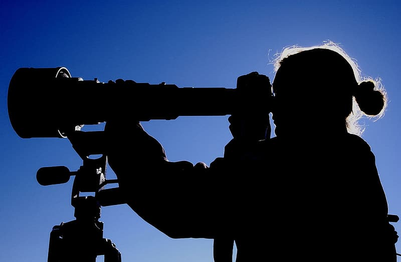 Silhouette photo of woman holding telescope