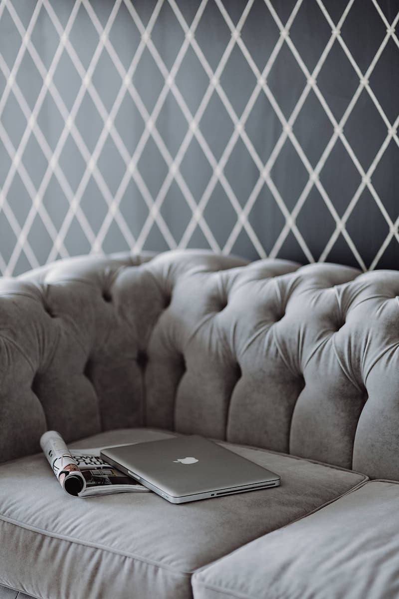 Silver macbook on brown couch