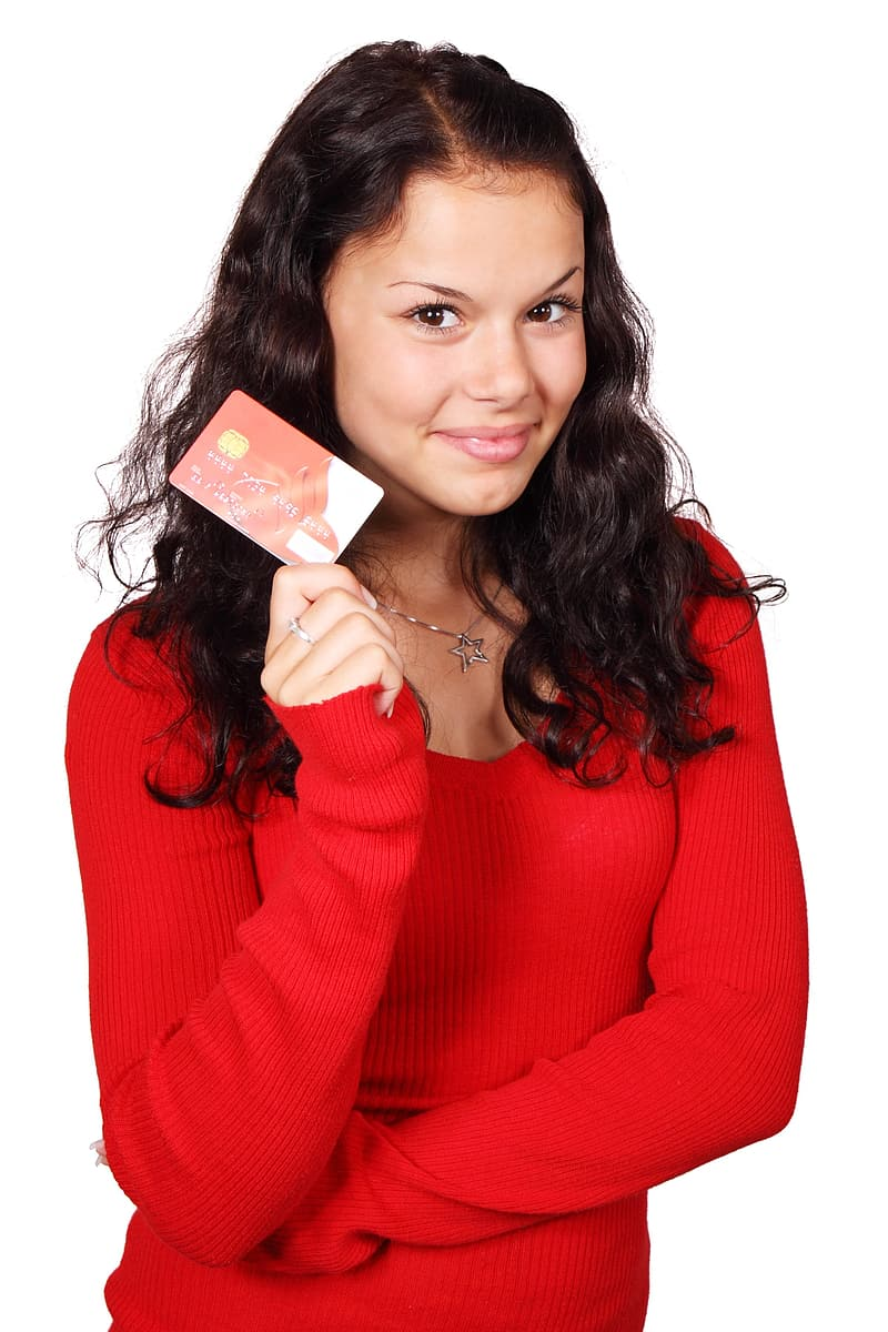 Woman wearing red sweater holding red and white magnetic card