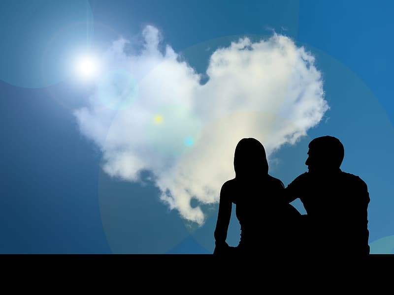 Silhouette of man and woman facing heart-shaped cloud