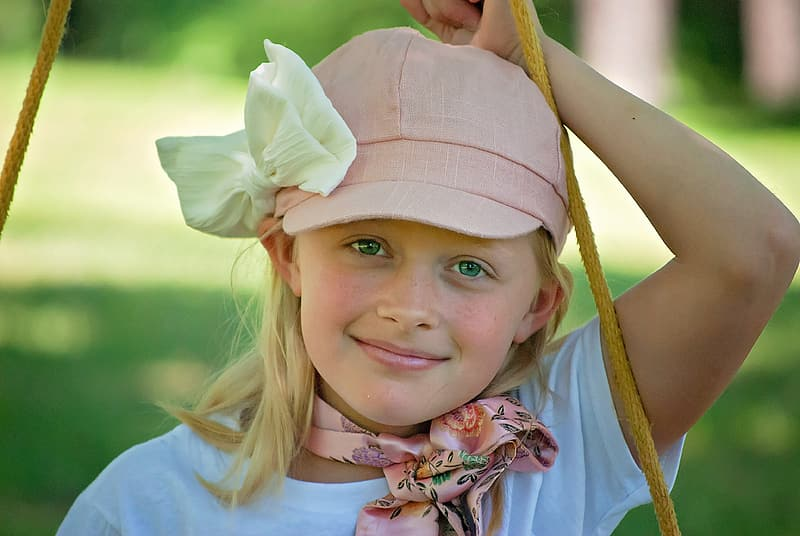 Woman wearing white crew-neck t-shirt and pink cap