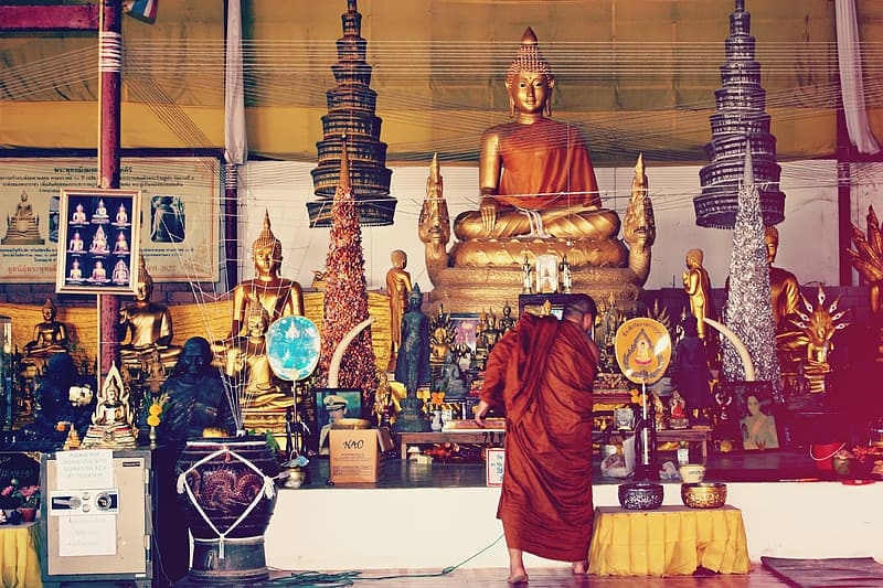 People in red robe standing in front of gold buddha statue