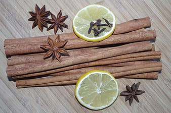 Cinnamon sticks and anis star with slices of lemons on surface