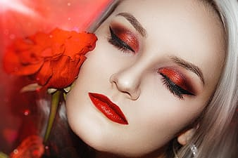 Woman with red lipstick holding red rose