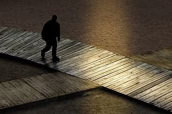 Silhouette of man walking on wooden dock during sunset