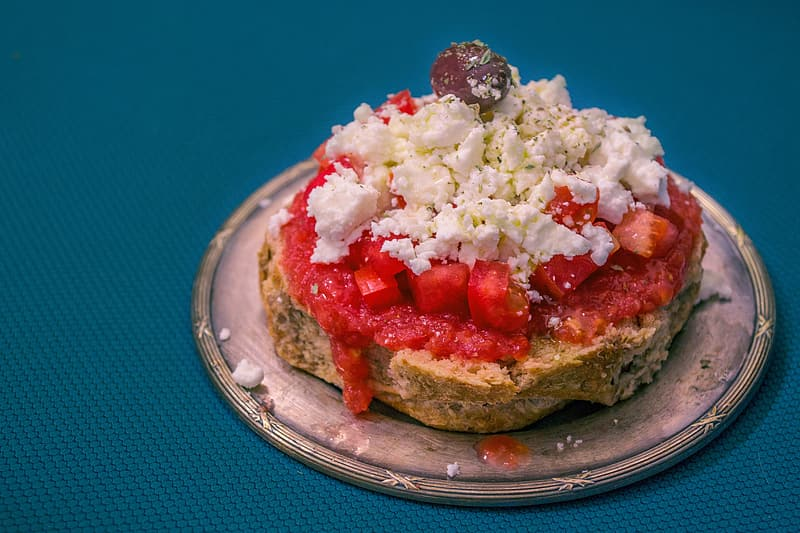 Bread with white cream and red sliced tomato on blue round plate