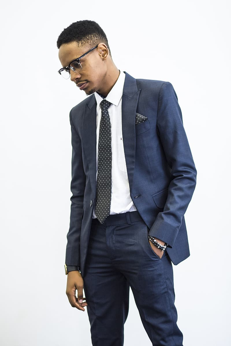Man wearing blue suit jacket and necktie looking at his right side