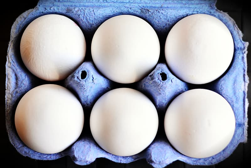 Six white eggs on purple tray