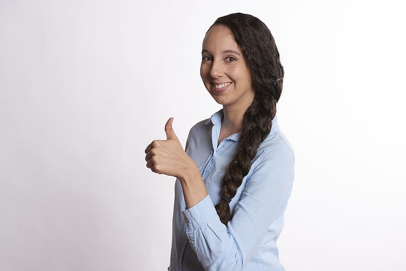 Woman in blue dress shirt in approve hand sign