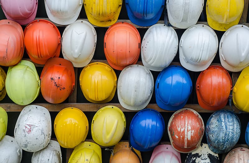 Assorted color of hardhats piled on brown wooden rack