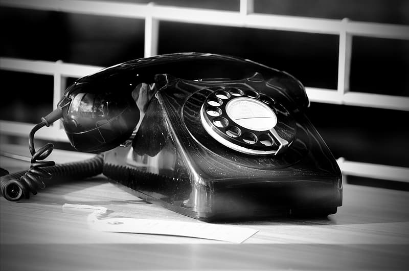 Grayscale photography of rotary telephone near white metal window grille