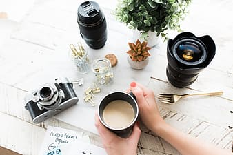 Person holding ceramic cup beside two camera lenses and SLR camera