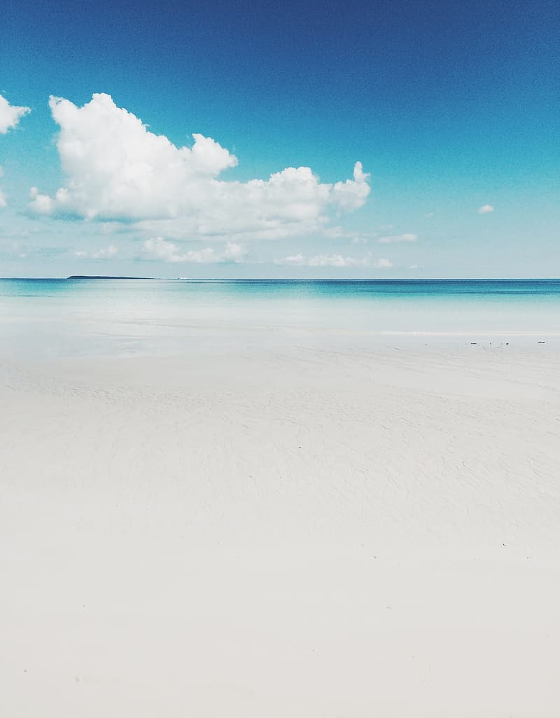 White sands near ocean water under sunny cloudy sky