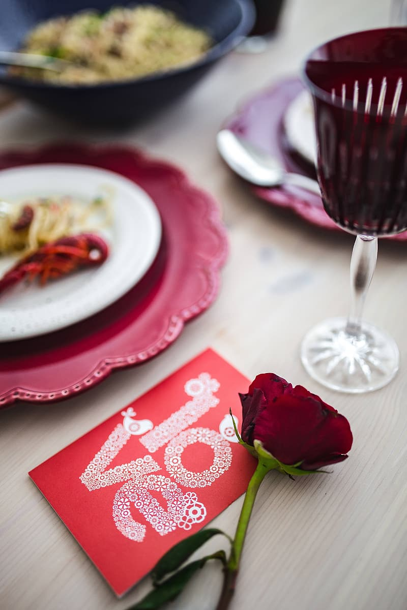 Red rose on white and red ceramic plate beside clear wine glass