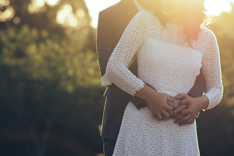 Man holding hands with woman on waist during sunset