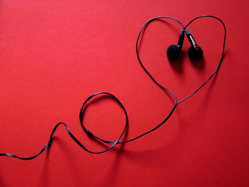 Black corded earphones on red surface
