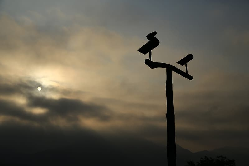 Silhouette of man standing on cross under cloudy sky during sunset