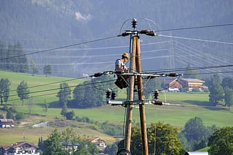 Man in black shirt and black pants standing on electric post during daytime