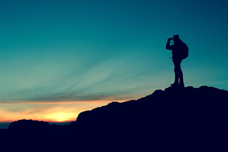Silhouette on man with backpack on mountain peak during golden house