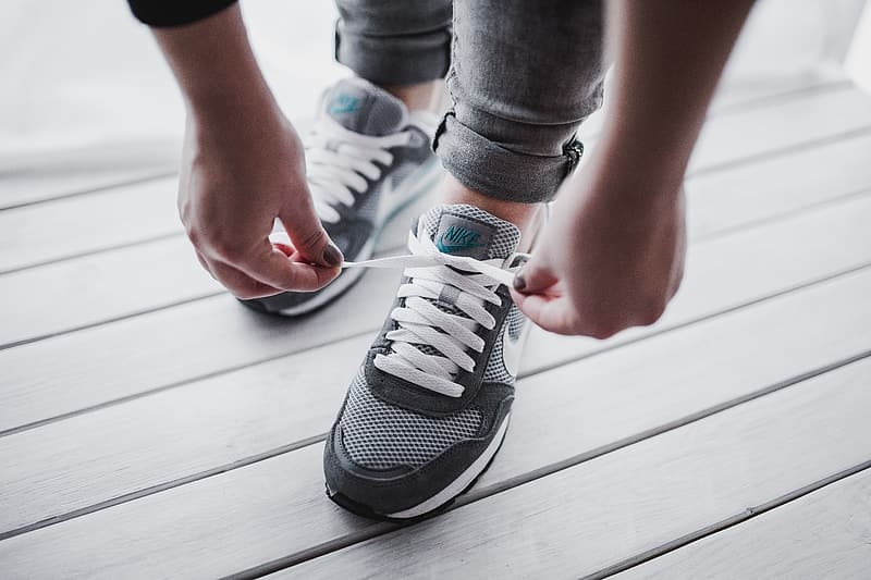 Person wearing gray and white nike sneakers