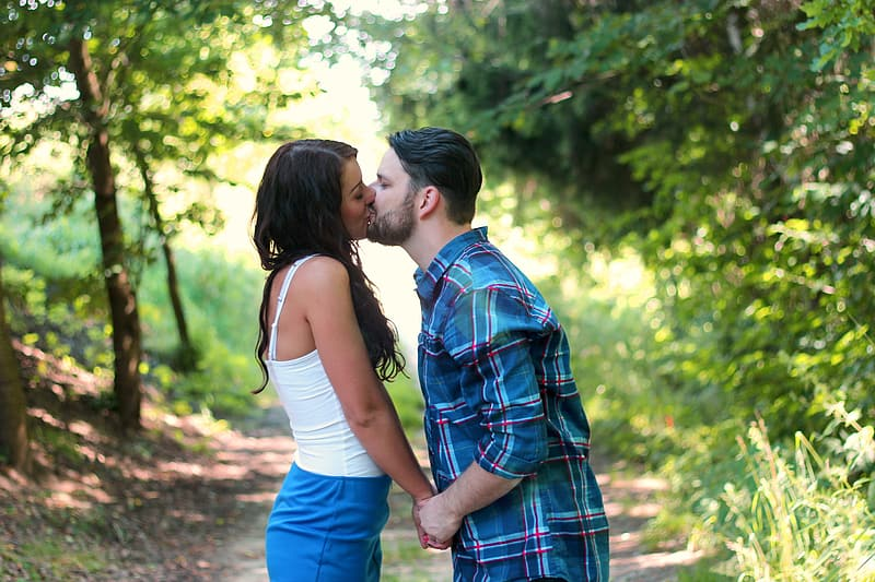 Couple kissing in forest during daytime
