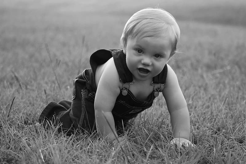 Grayscale photo of toddler crawling on grass
