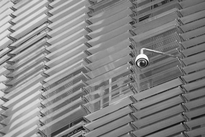White surveillance camera hanging