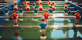 Close-up photo of green and blue foosball table