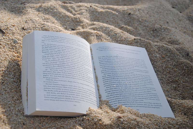 Opened book on brown sand