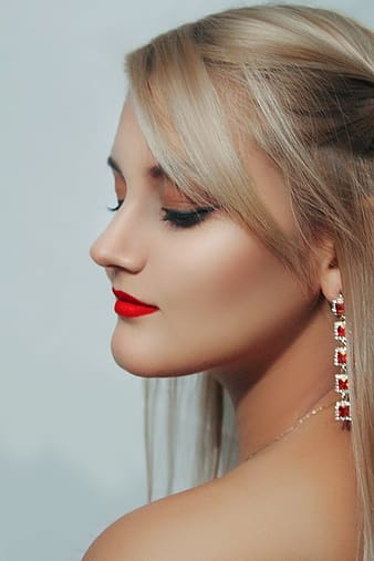 Woman wearing pink lipstick and silver-colored earring