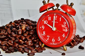 Red and gold alarm clock beside coffee beans