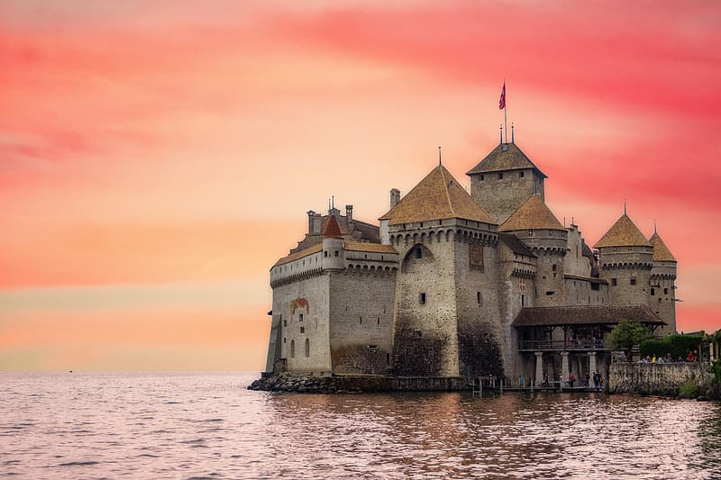 Brown concrete castle on body of water during daytime