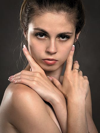 Woman with brown hair touching her face