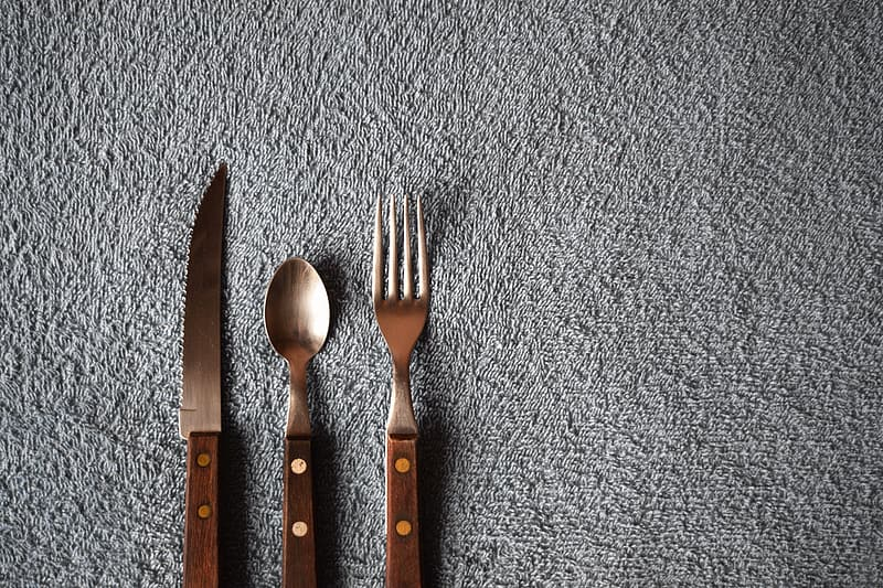 Brown handled cutlery on grey surface
