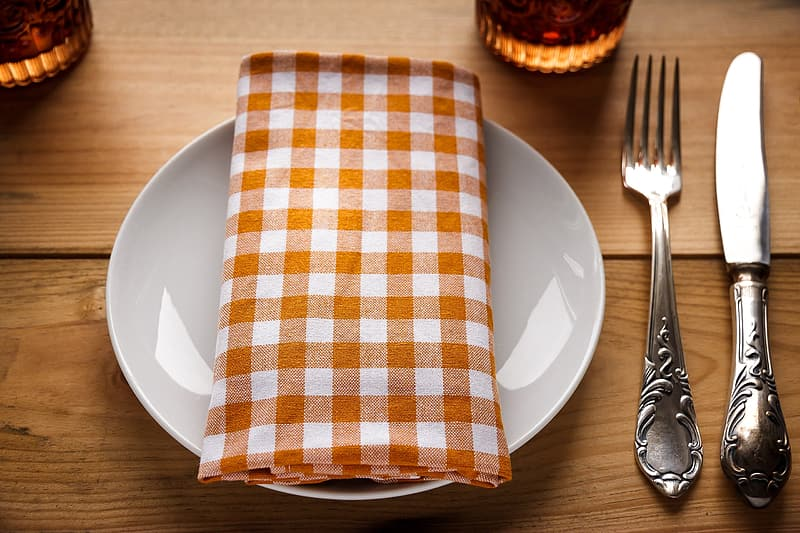 Orange and white gingham tablecloth on round white ceramic plate beside fork and knife
