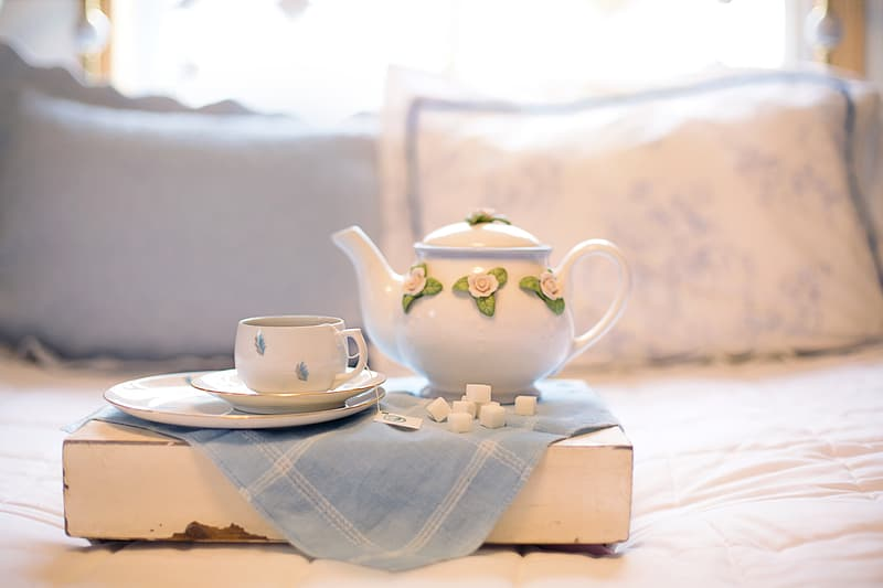 Shallow focus photography of white ceramic teapot beside teacup