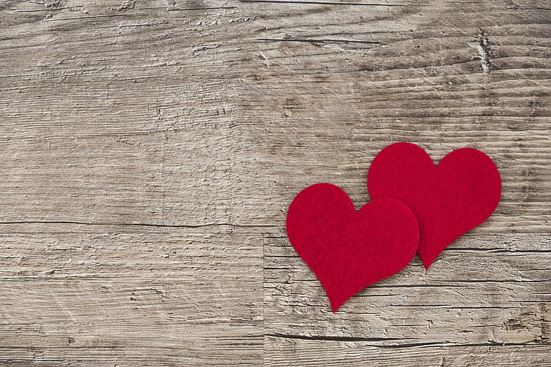 Two cutout hearts on brown wooden surface