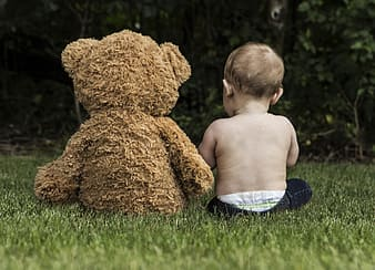 Toddler sitting together with brown bear plush toy