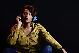Woman in green jacket and blue denim jeans sitting