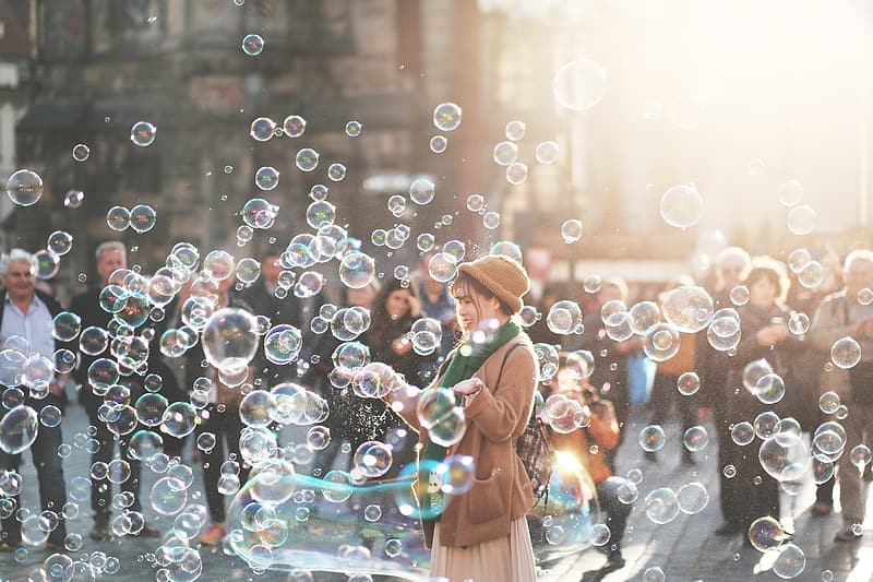 Woman in brown dress playing bubbles