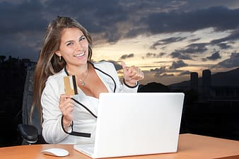 Woman wearing white blazer using MacBook White with credit card on her right hand outdoors
