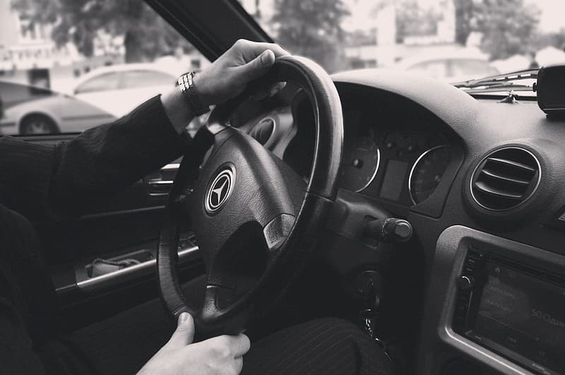 Greyscale photography of person holding Mercedes-Benz steering wheel