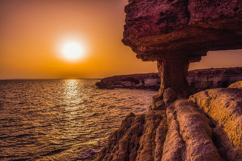 Brown rock formation near body of water during sunset