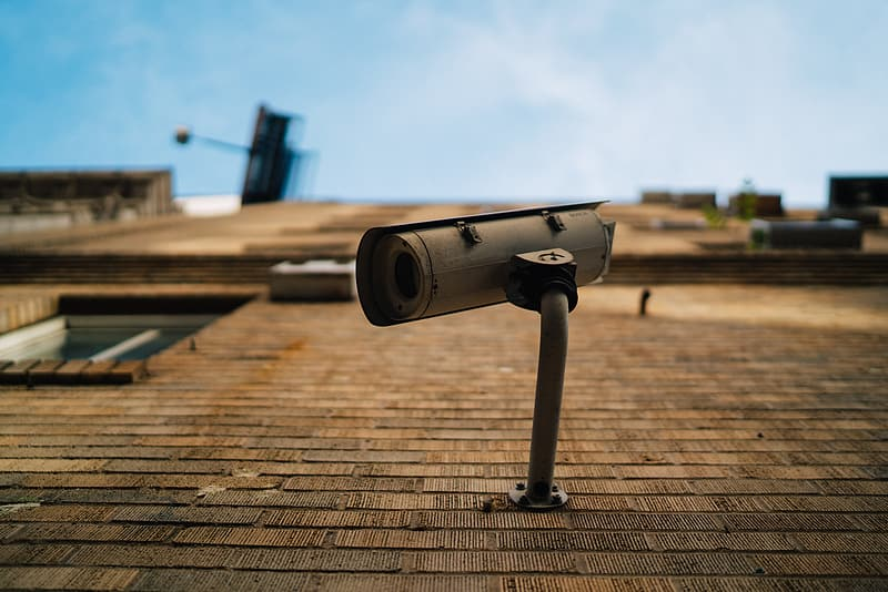 Selective focus photography of bullet security camera on brick wall