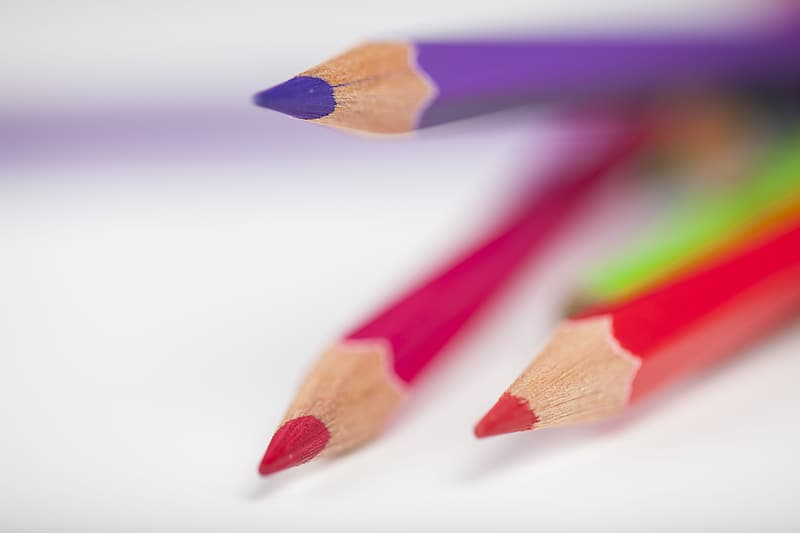 Three red, pink, and purple color pencils