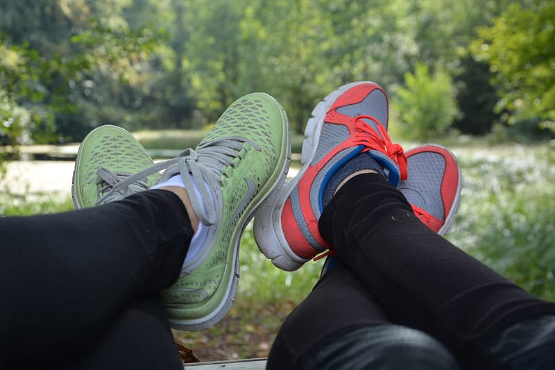 Two person showing pair of low-top sneakers near trees and grass during daytime