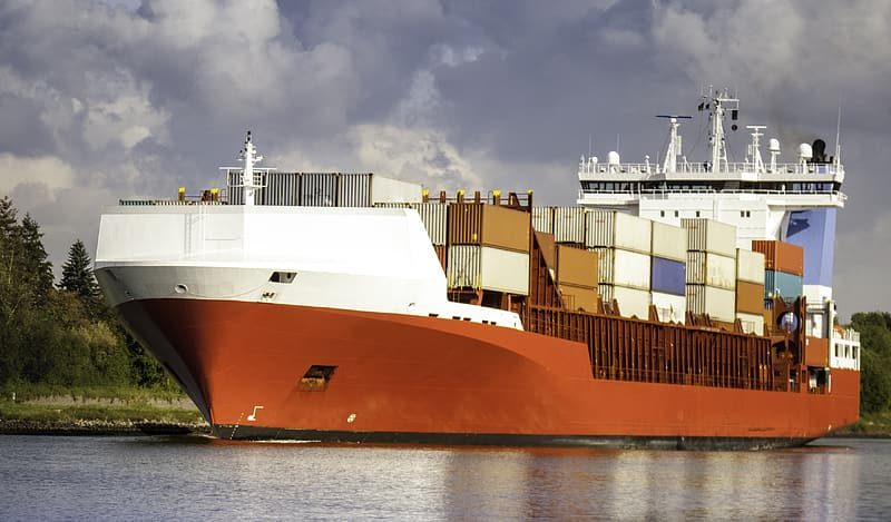 Brown and white cargo ship docked beside grass field